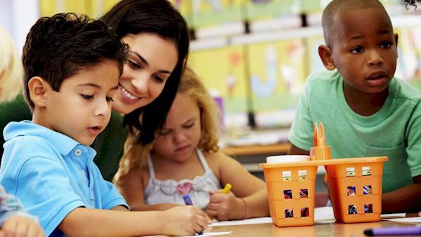Young Teacher Helping 3 Children at a Desk