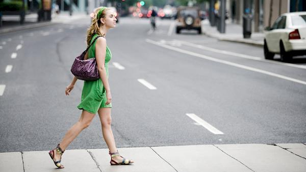 Stylishly Dressed Blonde Girl Crosses a Street in a Big City
