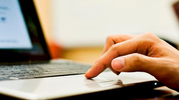 Person's Hand on the Touch Pad of a Laptop Computer