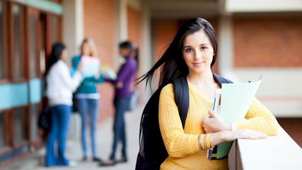 Female College Student Leaning on a Ledge Outside of a Building with other Students in the Background