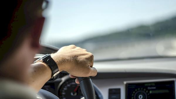 Looking Over the Right Shoulder of a Male Driver with his Hand on the Steering Wheel