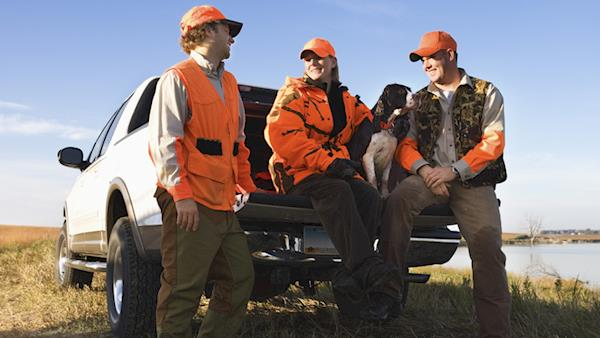 Three Hunters in Blaze Orange with their Bird Dog Sitting in the Back of a Pickup Truck Next to a Lake