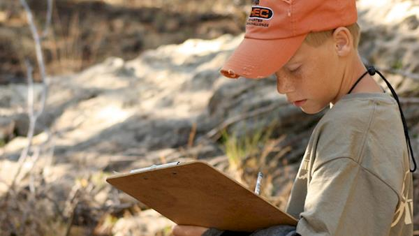 NRA Youth Hunter Education Challenge youth in an orange cap with a clipboard in the wilderness