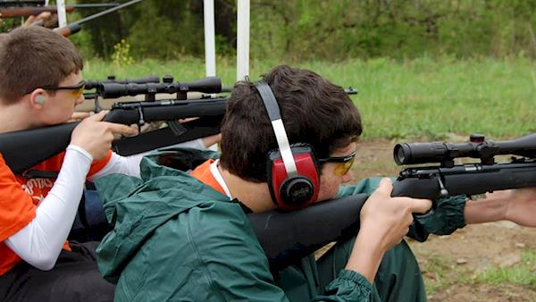 Young men wearing ear protection shooting scoped rifles at a range.