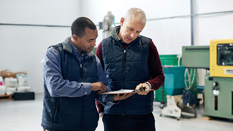 Two men in a workshop looking at a clip board