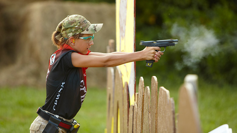 Young Competitive Shooter Firing Her Pistol at an Outdoor Range