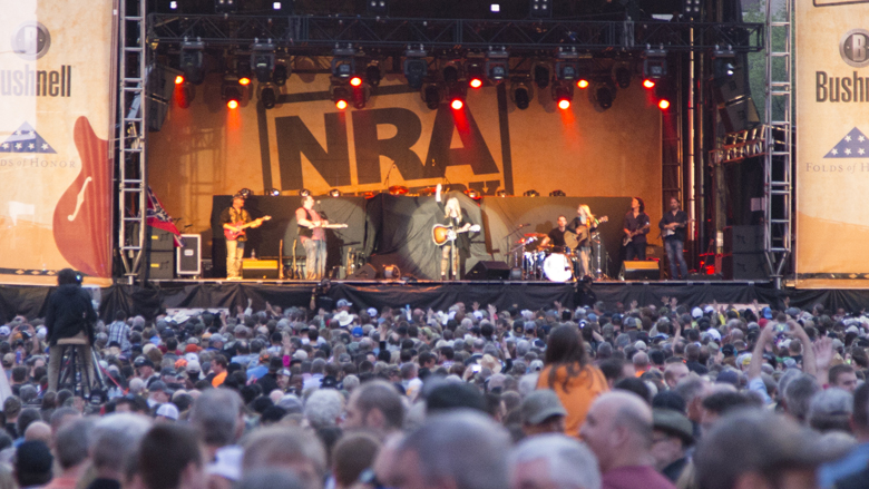 NRA Country Stage with a country band playing music in front of a huge crowd.