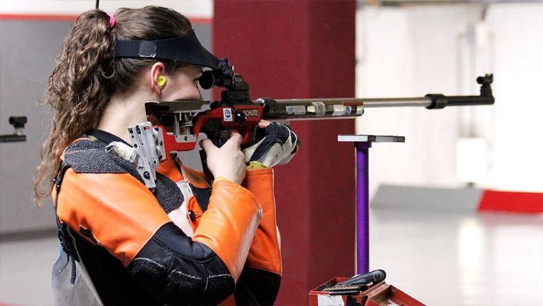 Young collegiate shooting competitor at an indoor range.