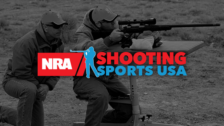 NRA Shooting Sports USA Logo on top of darkened image of a man shooting a rifle with a spotter by his side