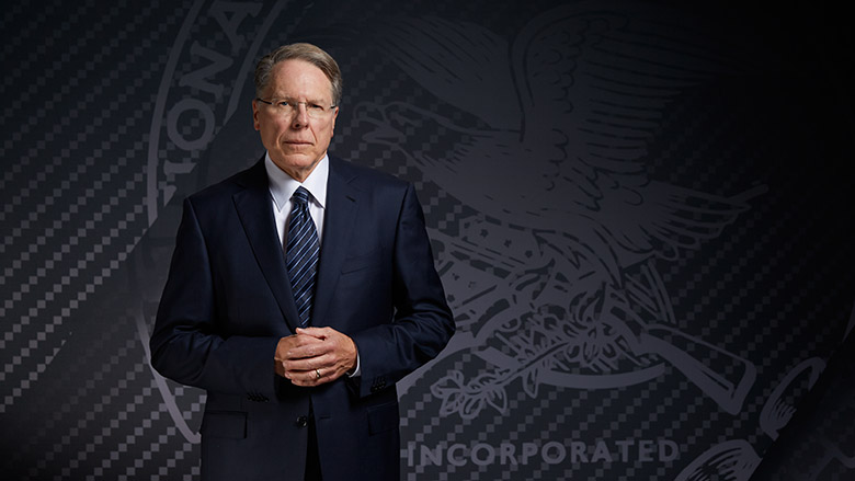 Wayne LaPierre in a dark suit standing in front of the NRA emblem