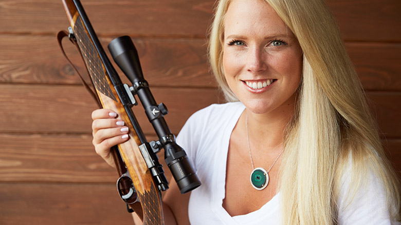 Woman smiling while holding her scoped rifle