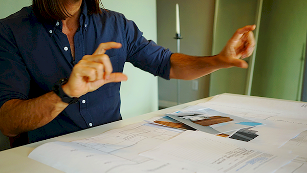 Person Reviewing Architectural Plans While Making Their Point