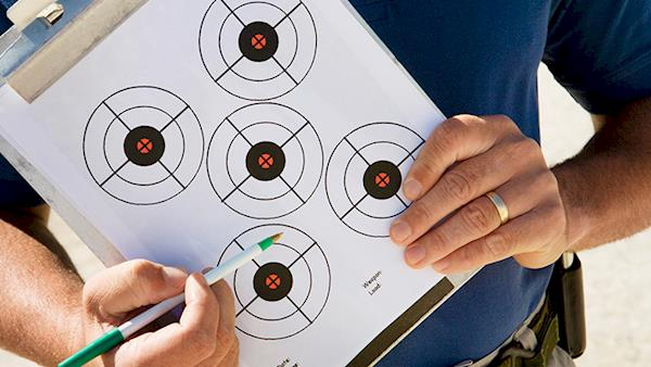 NRA Instructor Pointing to a Target on his Clipboard.