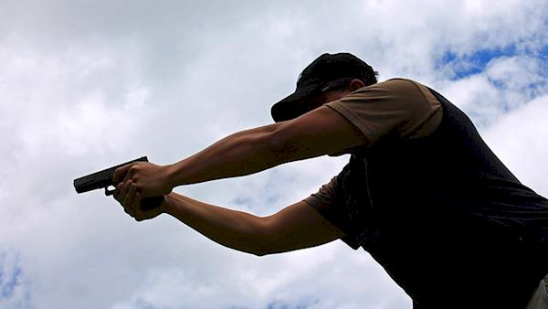 Silhouette of a Man Shooting a Pistol Outside