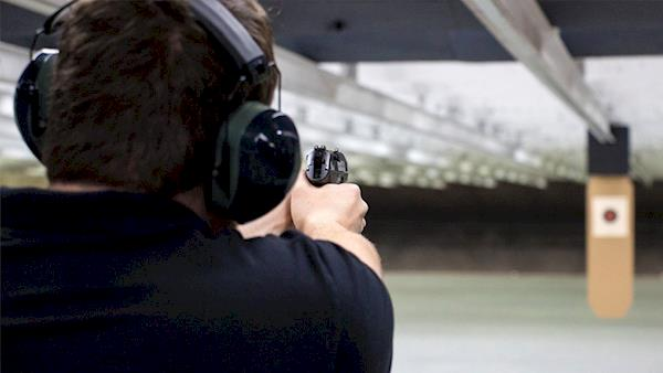 Looking Over the Right Shoulder of a Shooter Shooting at an Indoor Range at a Paper Target
