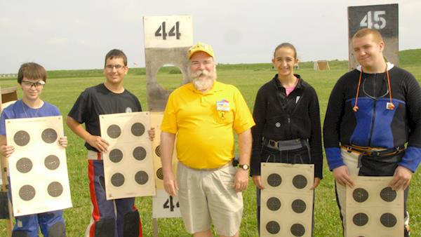 Lineup of Young Competitors Holding up Their Targets with Their Coach
