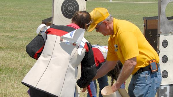 Man in a Yellow Shirt and Cap helping a Competitor with their Target