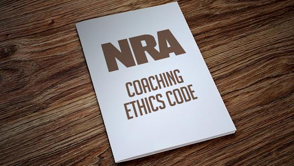 NRA Coaching Ethics Code Manual Laying on a Wooden Desk