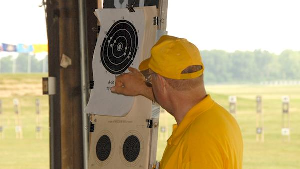Coach Looking at the Grouping of Shots on a Paper Target at an Outdoor Range