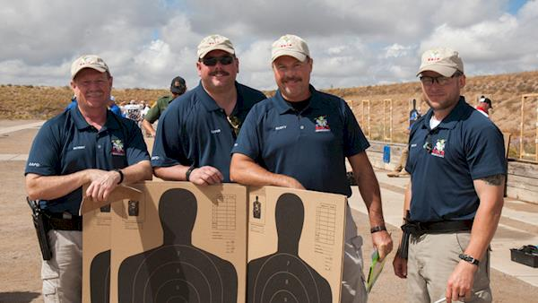 Four Competitors Proudly Standing Behind Their Silhouette Targets After a Match