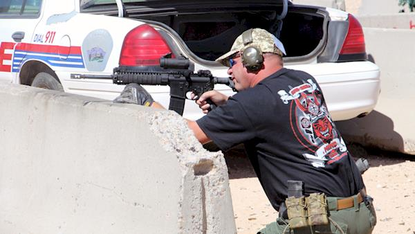 Tactical Police Competition Competitor shooting from Behind a Barricade