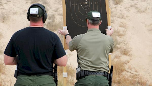Competitor Removing Their Target from an Outdoor Range To Be Reviewed