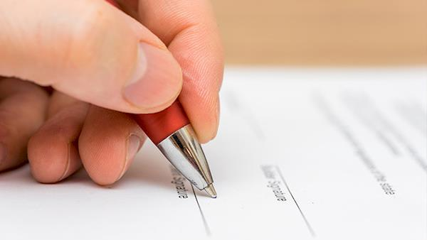 Closeup of a Person with a Pen Filling Out Paper Work