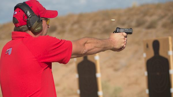 Competitor in a Red Polo Shirt and Cap Firing at Silhouette Targets on an Outdoor Range
