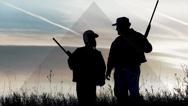 Silhouette of a Father and Son with Shotguns Hunting at Dawn