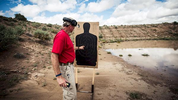 Firearm Instructor Examining Shot Grouping on a Silhouette Target at an Outdoor Range