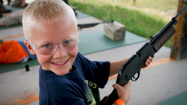 Happy Young Blond Boy with Big Smile, Safety Glasses and his Air Rifle at an Outdoor Range