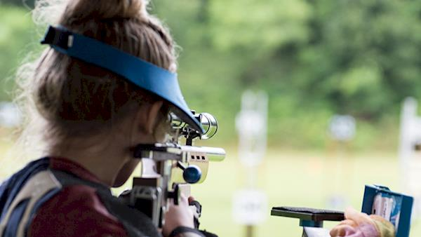 Female Collegiate Shooting Competitor Looking at Target Through Her Rifle Scope at an Outdoor Range
