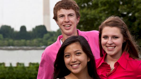 Three Smiling Young People Standing In Front of the Washington Monument