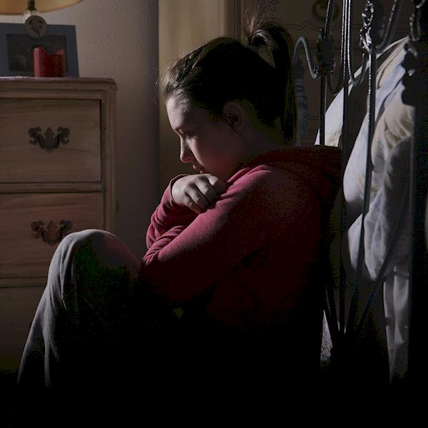 Young Girl Sitting In The Dark