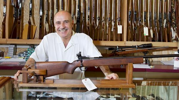 Smiling Gun Shop Owner Displaying a Rifle