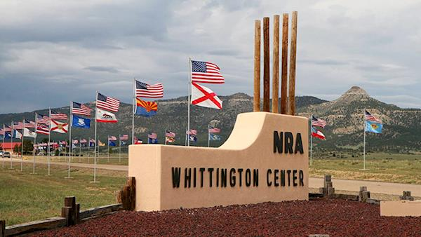 Entrance Way to the NRA Whittington Center with Flags and Mountains in the Background