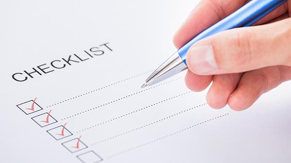 A hand with a pen ticking off boxes in a checklist