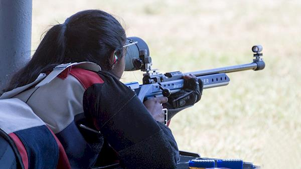 Female Competitor Shooting a Rifle at an Outdoor Range