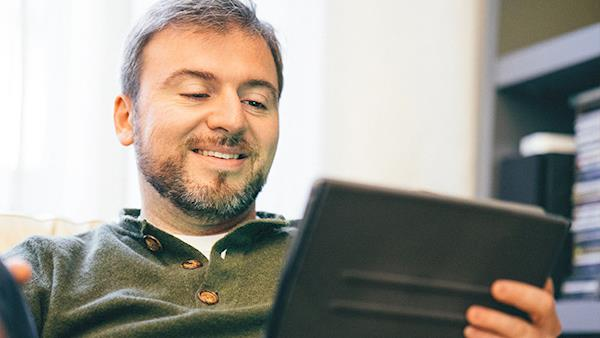 Bearded Man Smiling While Looking at his Tablet