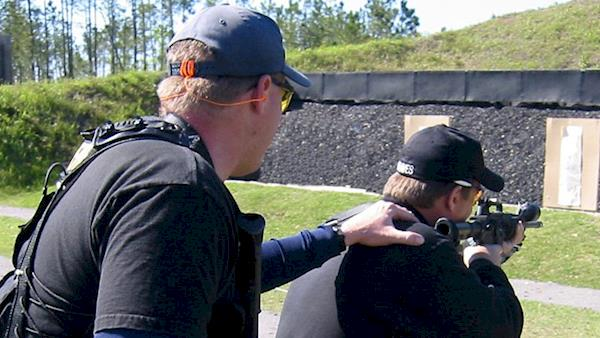 Two men training on an outdoor rifle range.