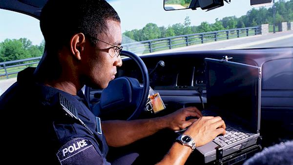 Police officer using his laptop inside his squad car.