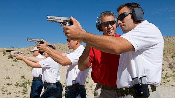 NRA Instructor Working with People in a Firing Line at an Outdoor Gun Range in the Desert