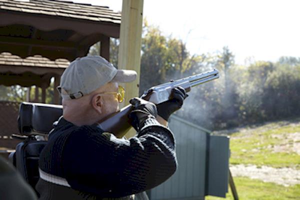 Man in a tan baseball cap shooting a shotgun from a wheelchair.