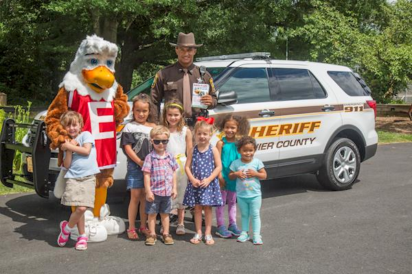 Eddie Eagle Mascot With Children and a Sheriff Outside Standing in Front of a Sheriff Vehicle