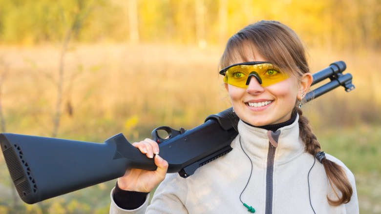 Young girl smiles while carrying a shotgun in a field over her shoulder.