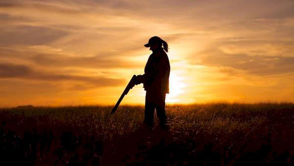 Sunset Silhouette of a Female Hunter Reloading Her Shotgun